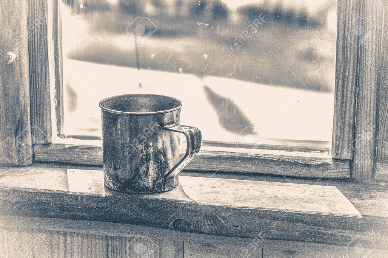 Old vintage photo. Old metal mug stands on a wooden window sill